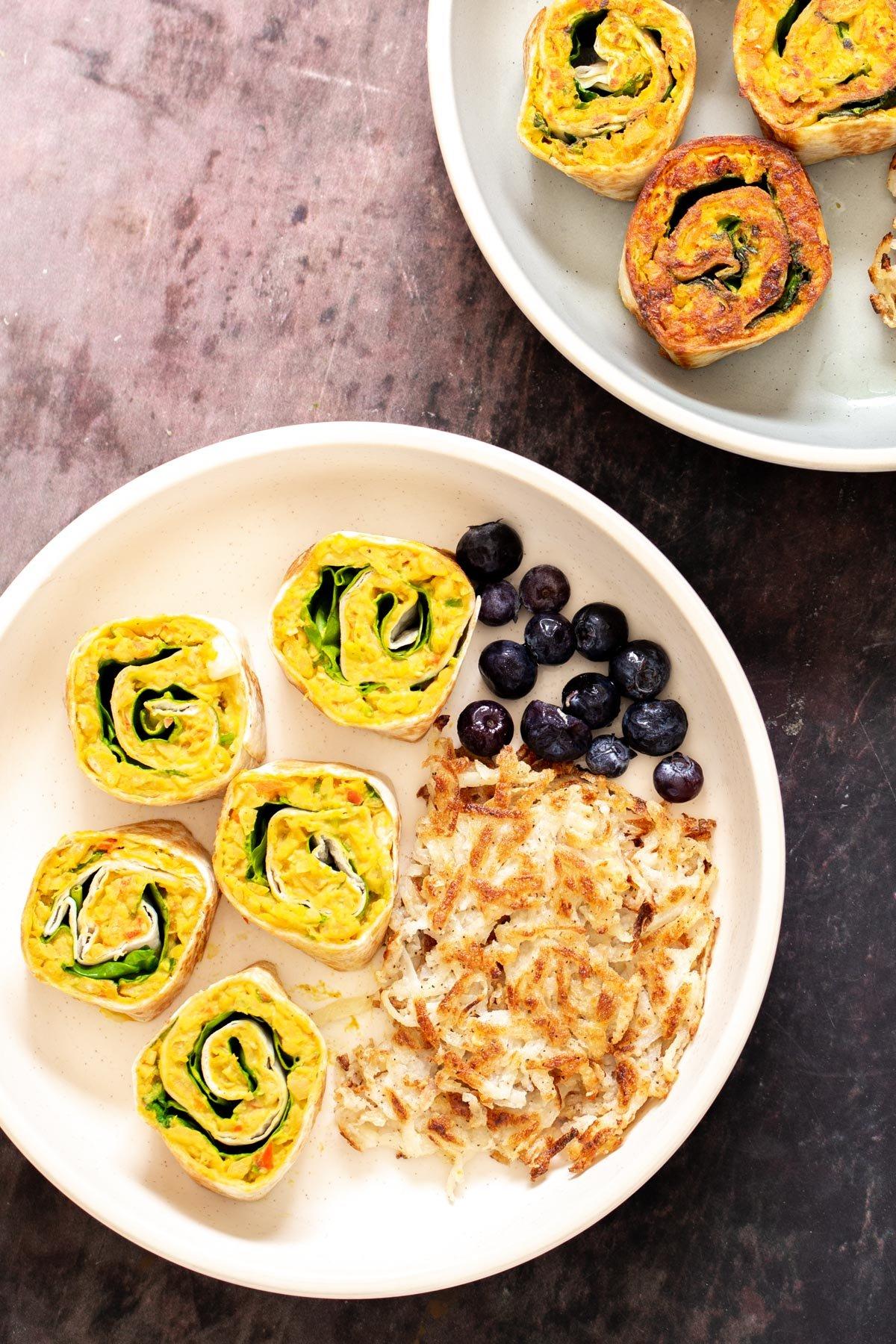 vegan chickpea breakfast platter with vegan chickpea scramble pinwheels, hash brown and berries