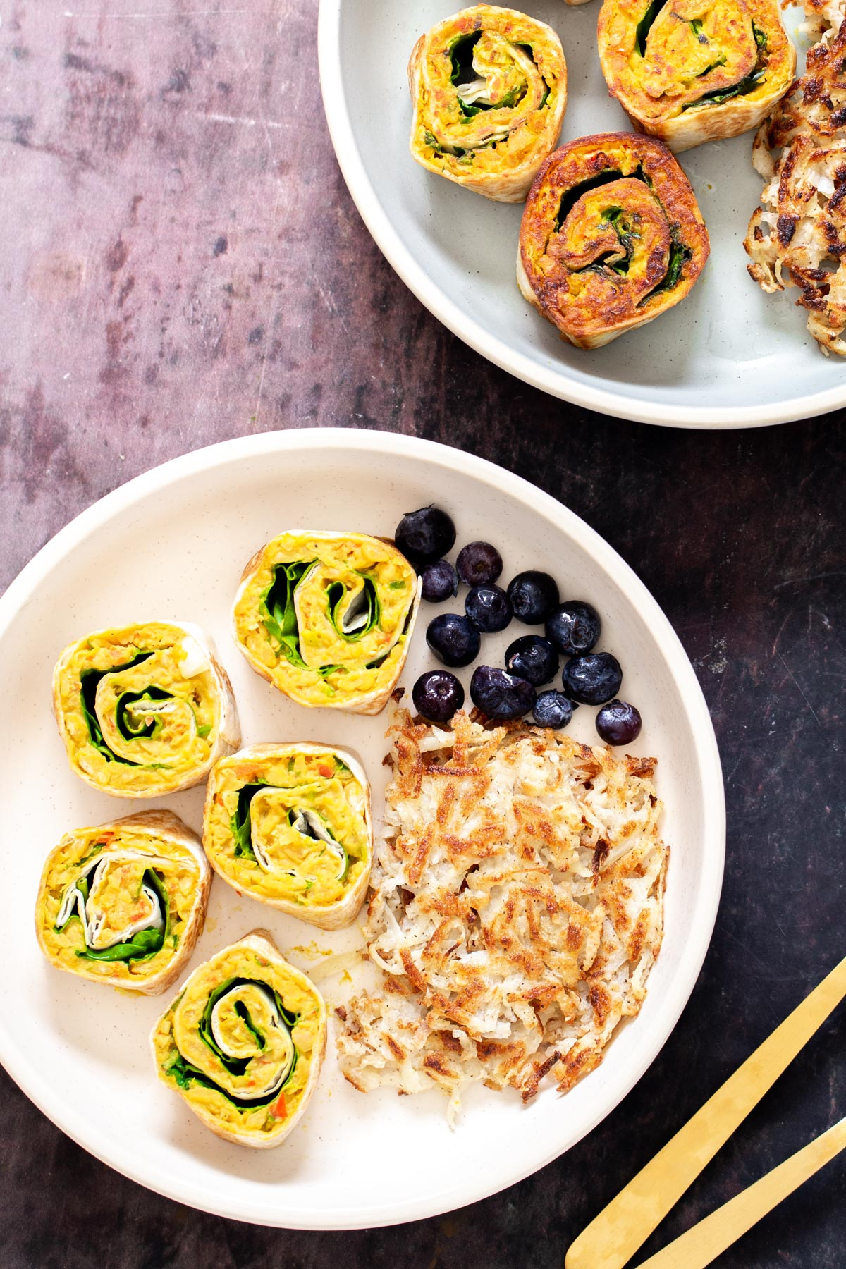 vegan chickpea scramble pinwheels served with blueberries and hashbrowns