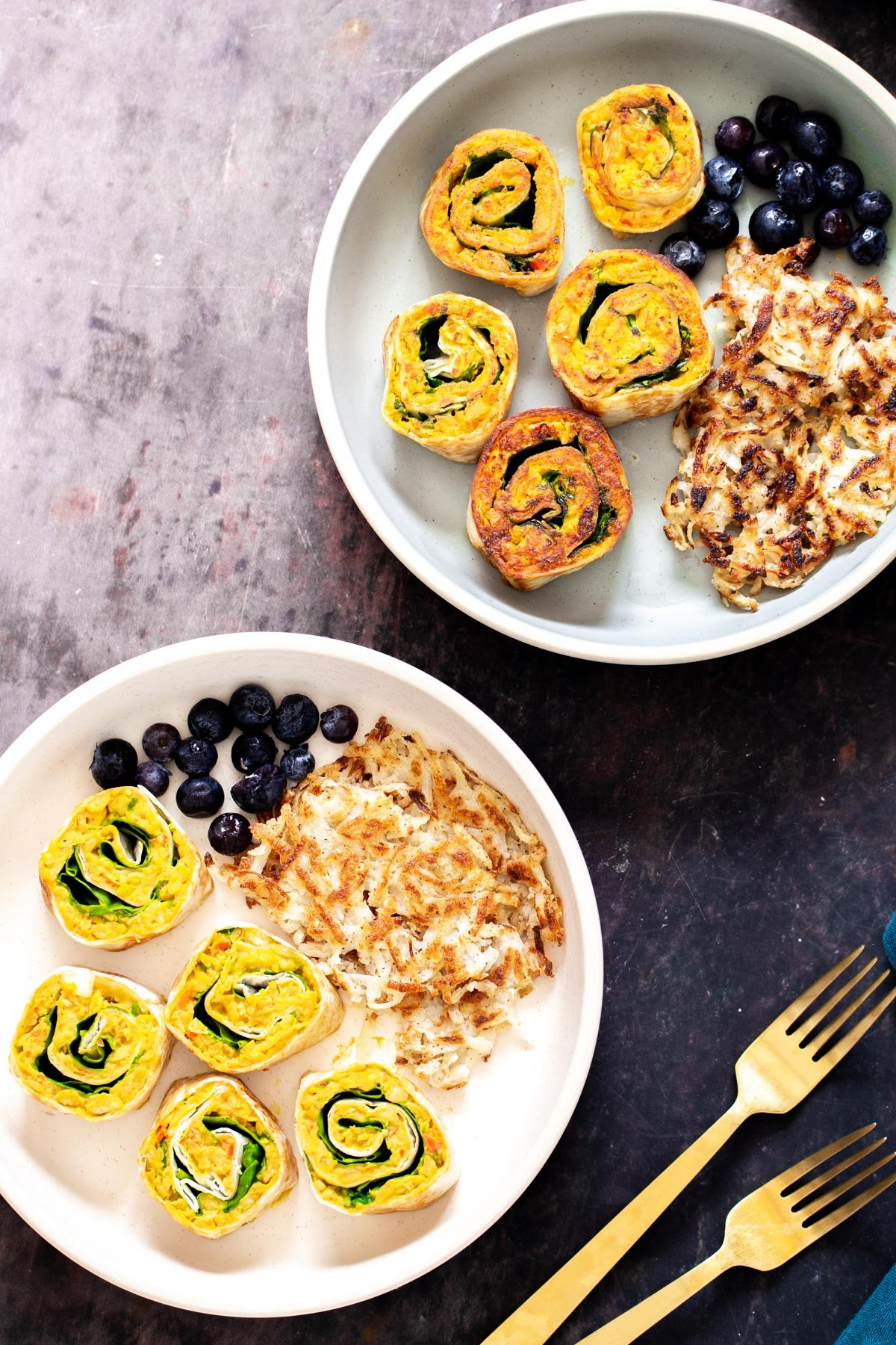 two plates with vegan chickpea breakfast scramble pinwheels served with berries and hashbrowns