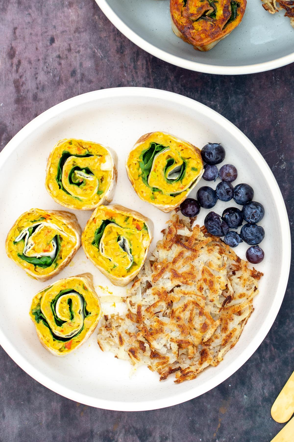 vegan chickpea breakfast rolls served on a plate with blueberries and hashbrowns