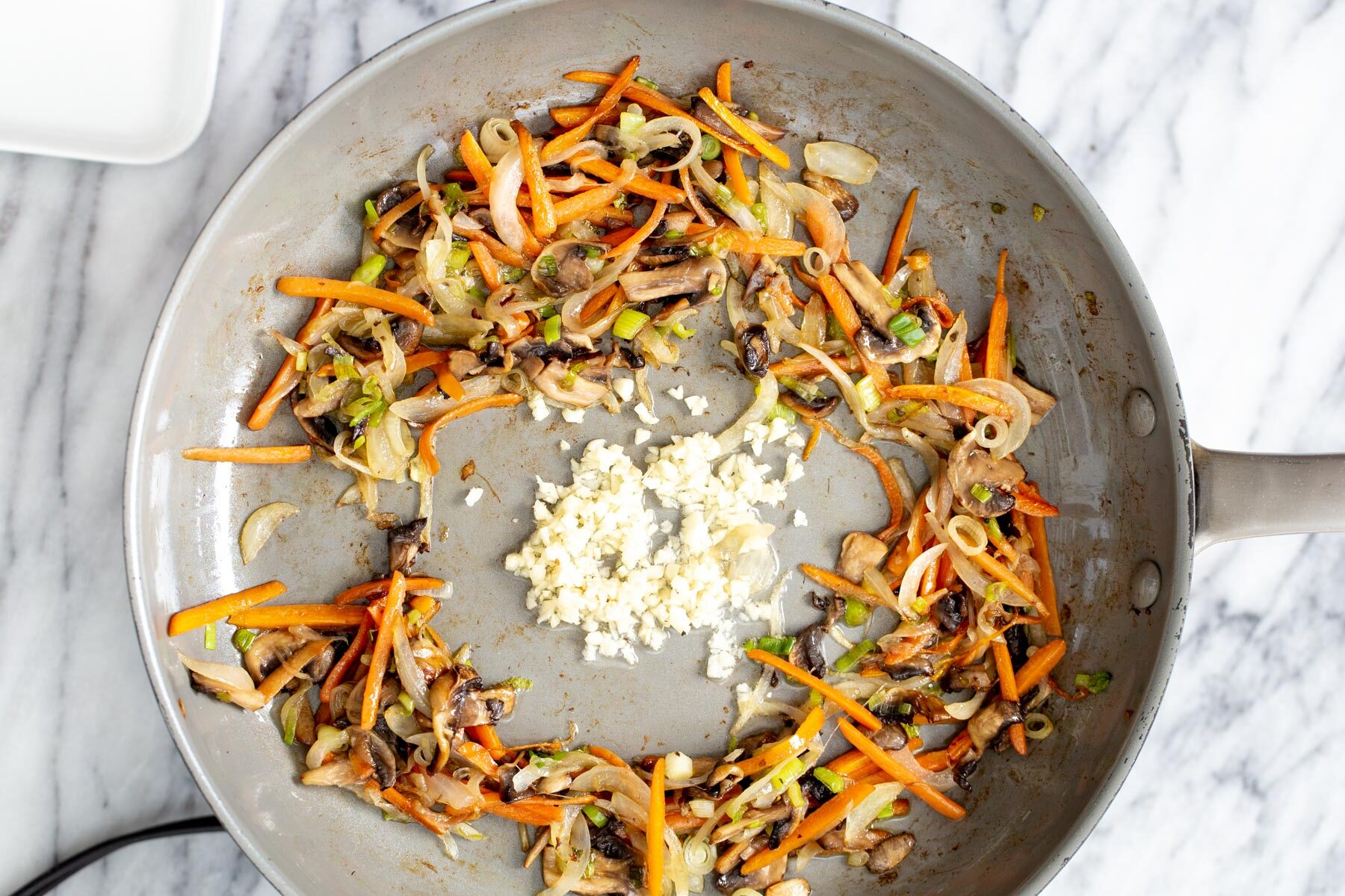 finely sliced veggies stir-frying with garlic in a saucepan