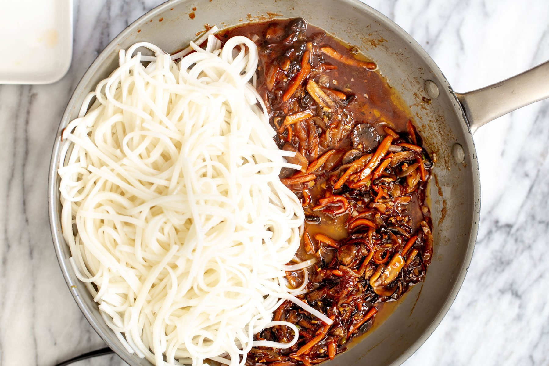 cooked rice noodles and veggies with Korean stir-fry sauce in a saucepan