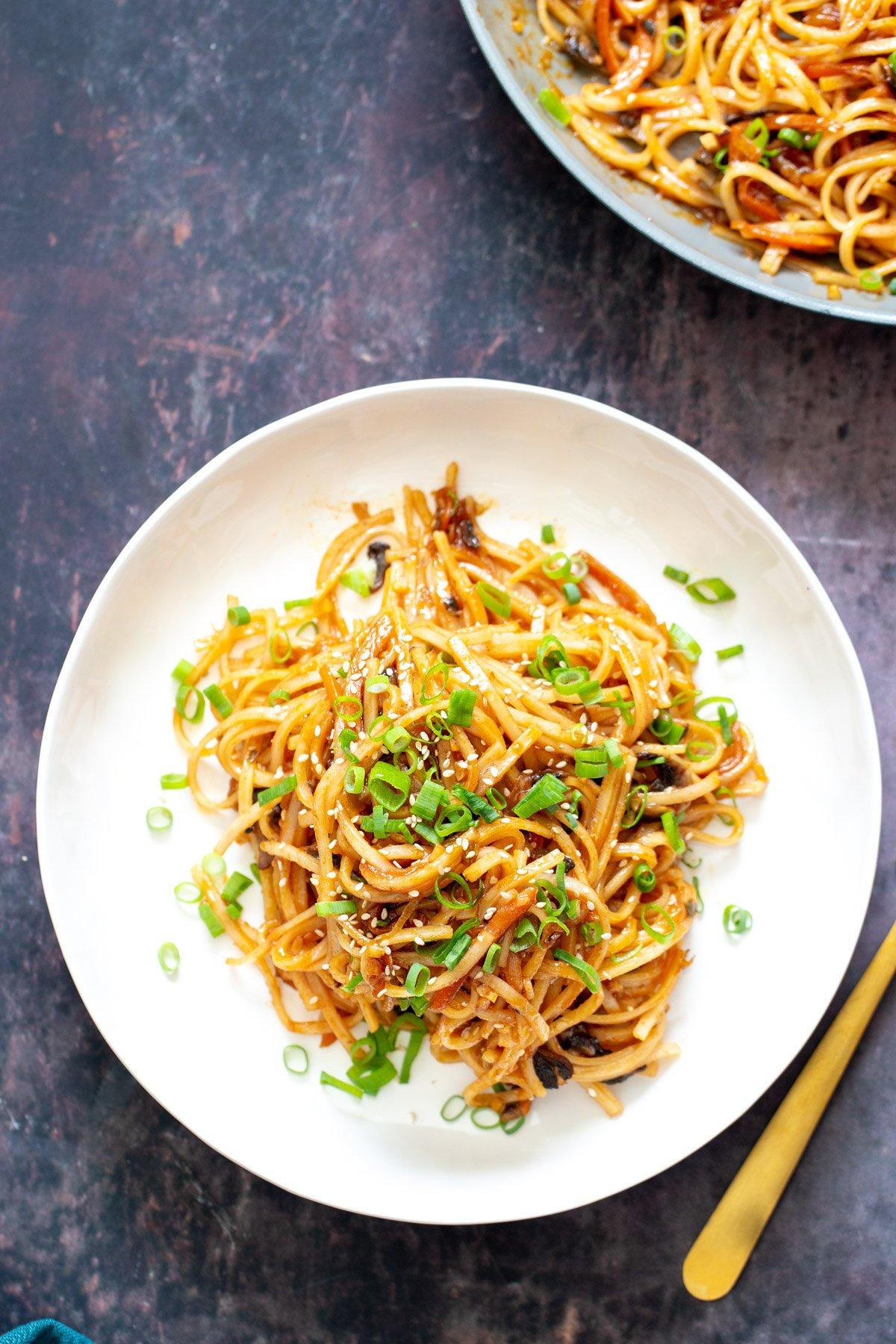 a plate of gochujang noodles topped with sliced spring onions and sesame seeds