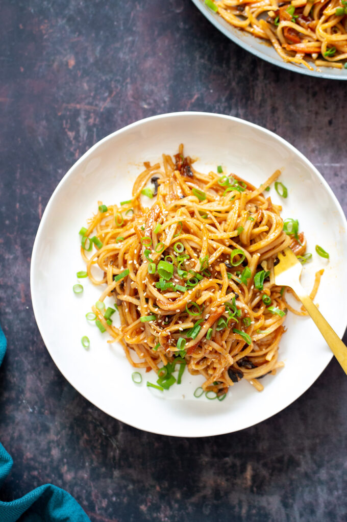 a plate of gochujang noodles sprinkled with sliced scallions
