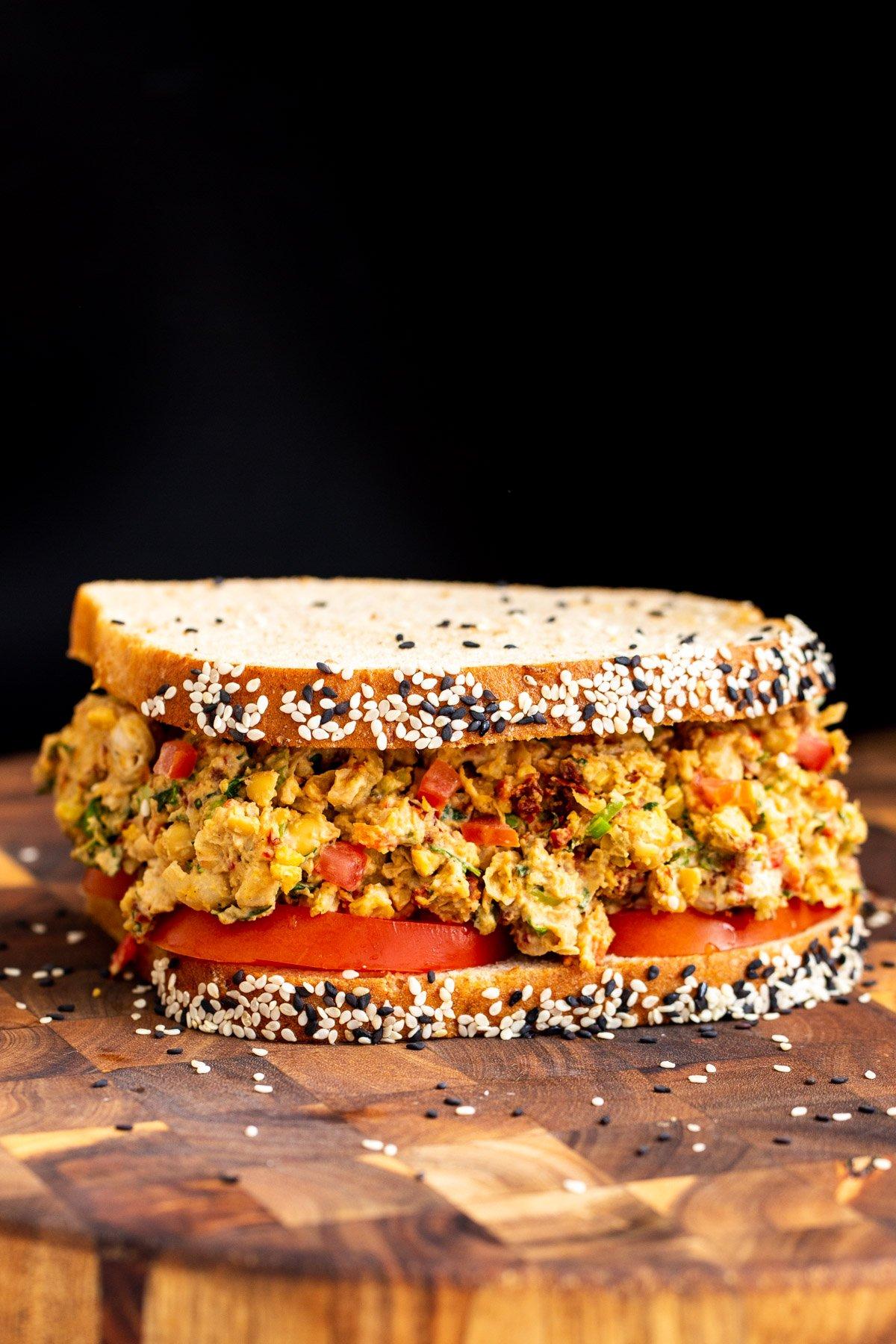 vegan Mediterranean chickpea salad sandwich on multigrain bread served on a wooden board