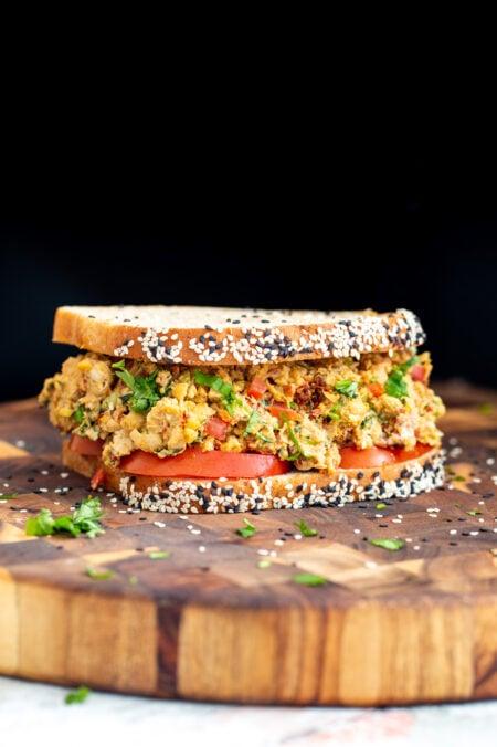 Mediterranean chickpea salad sandwich on a wooden board