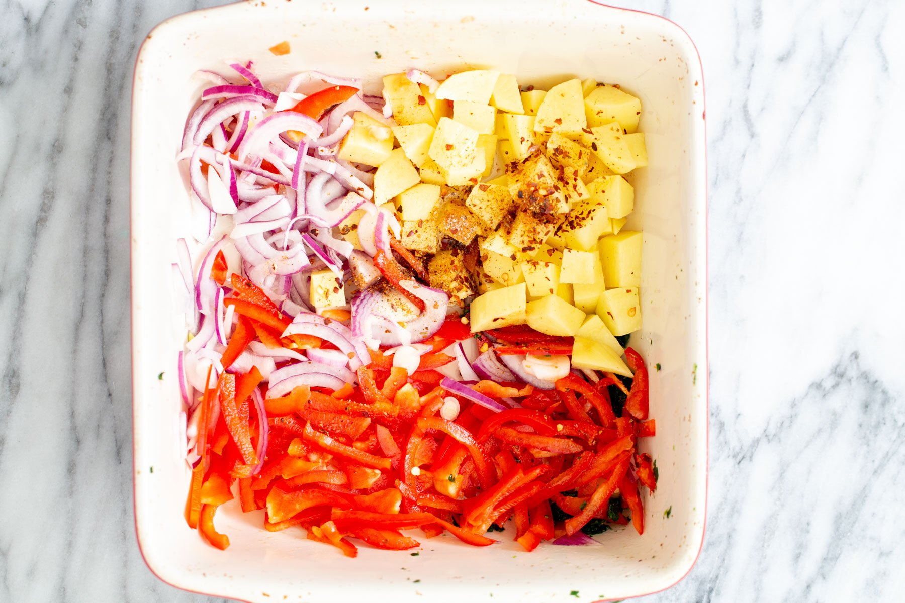 sliced onion and bell pepper and cubed potatoes in a white casserole dish