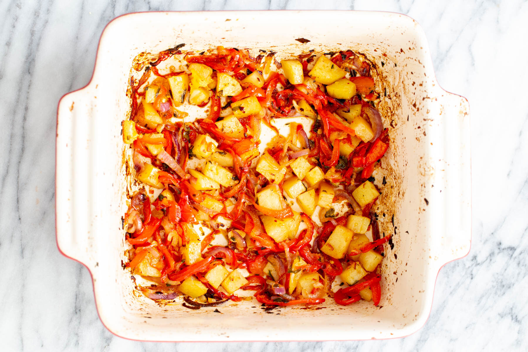 roasted bell peppers, onion and potatoes in a casserole dish