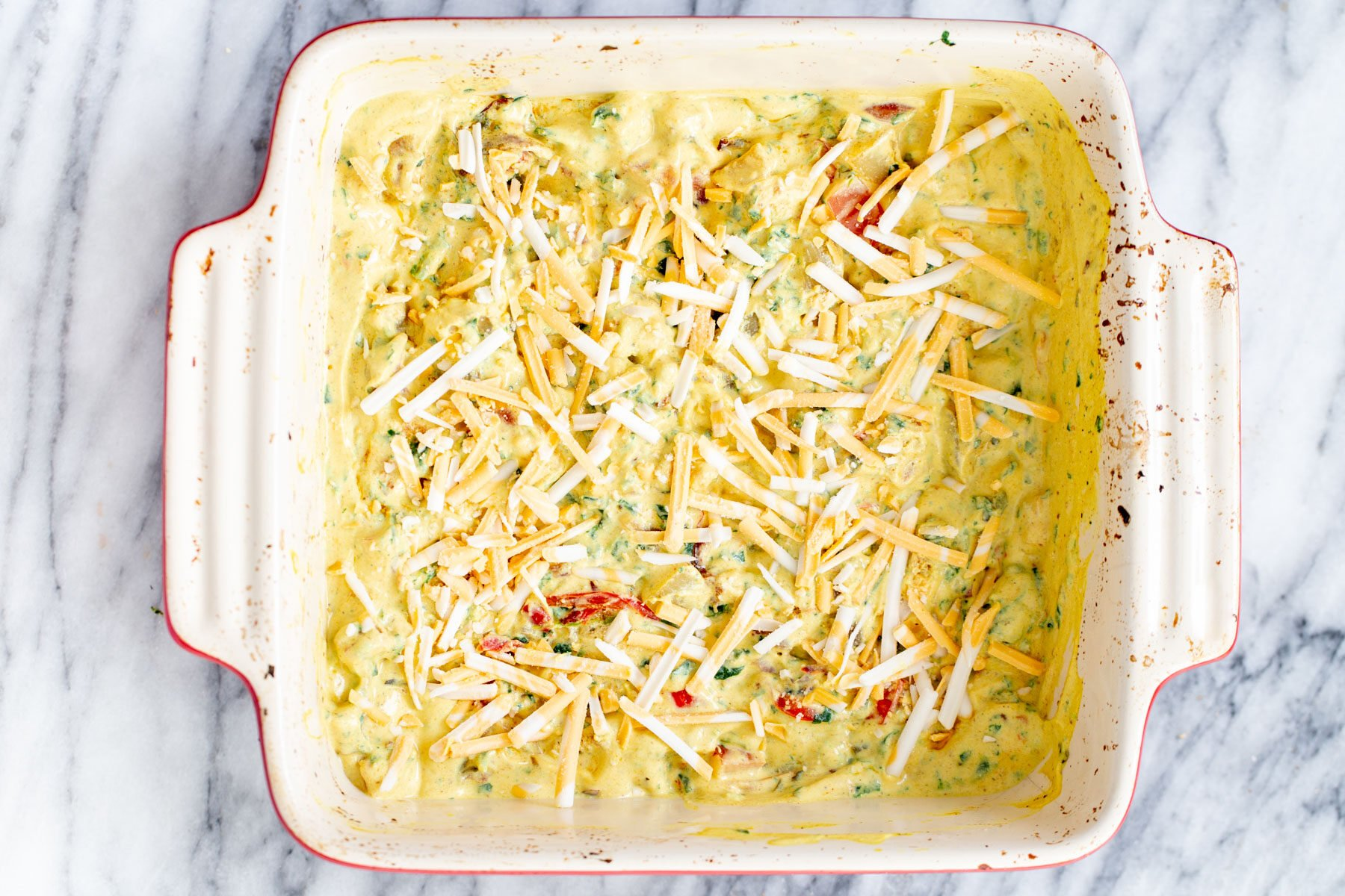vegan egg breakfast casserole being topped with shredded cheese