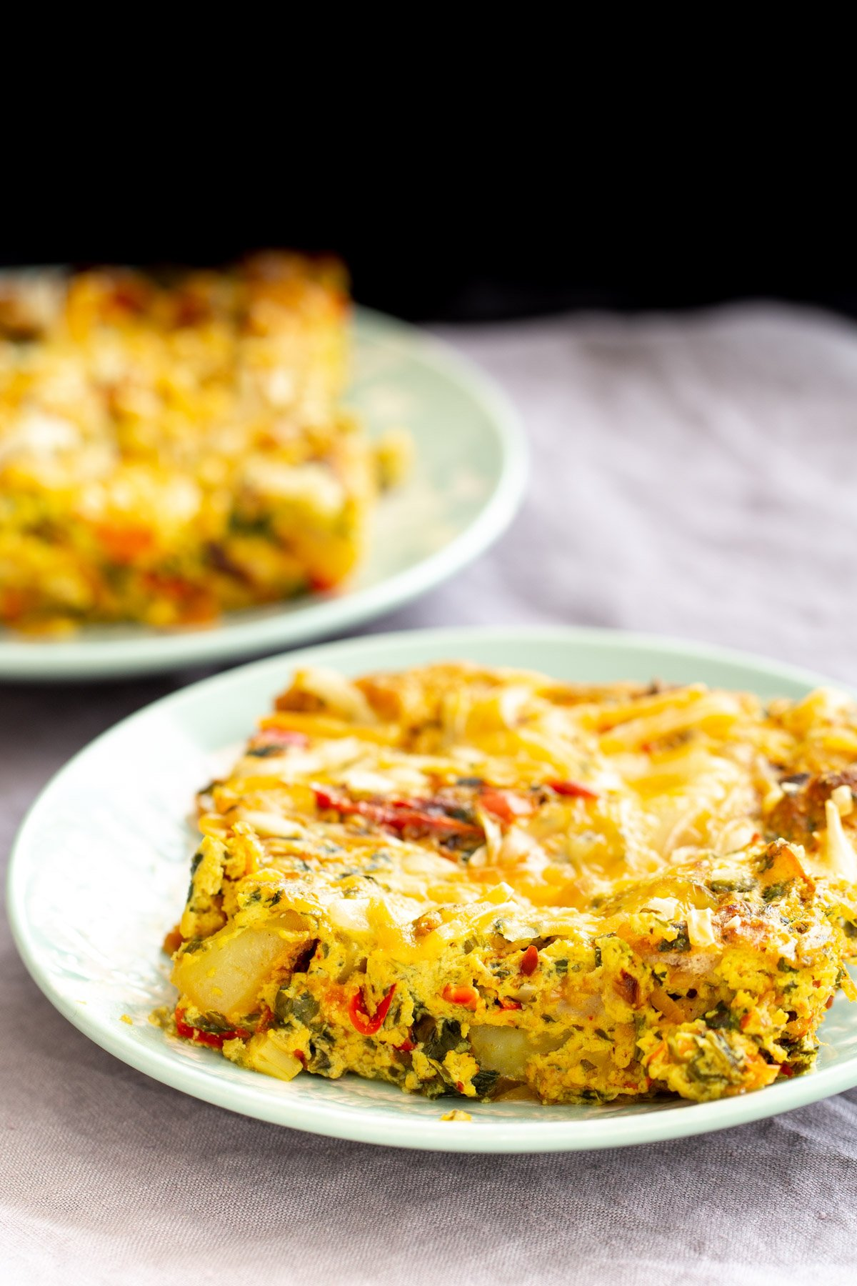 two plates with vegan Mexican egg breakfast casserole with bell pepper, potatoes and onions