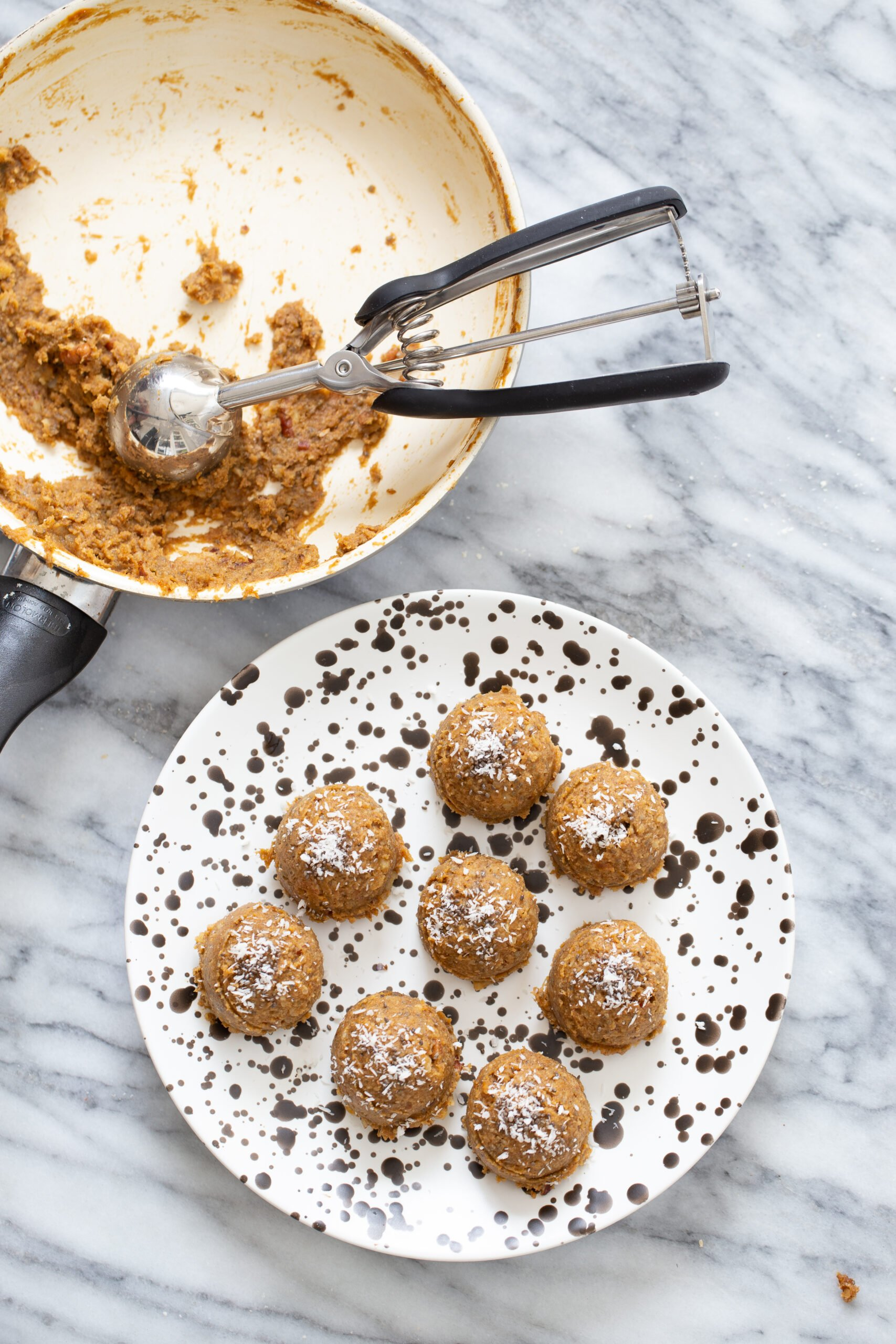 pumpkin pie energy balls on a white plate with cookie scoop in a skillet