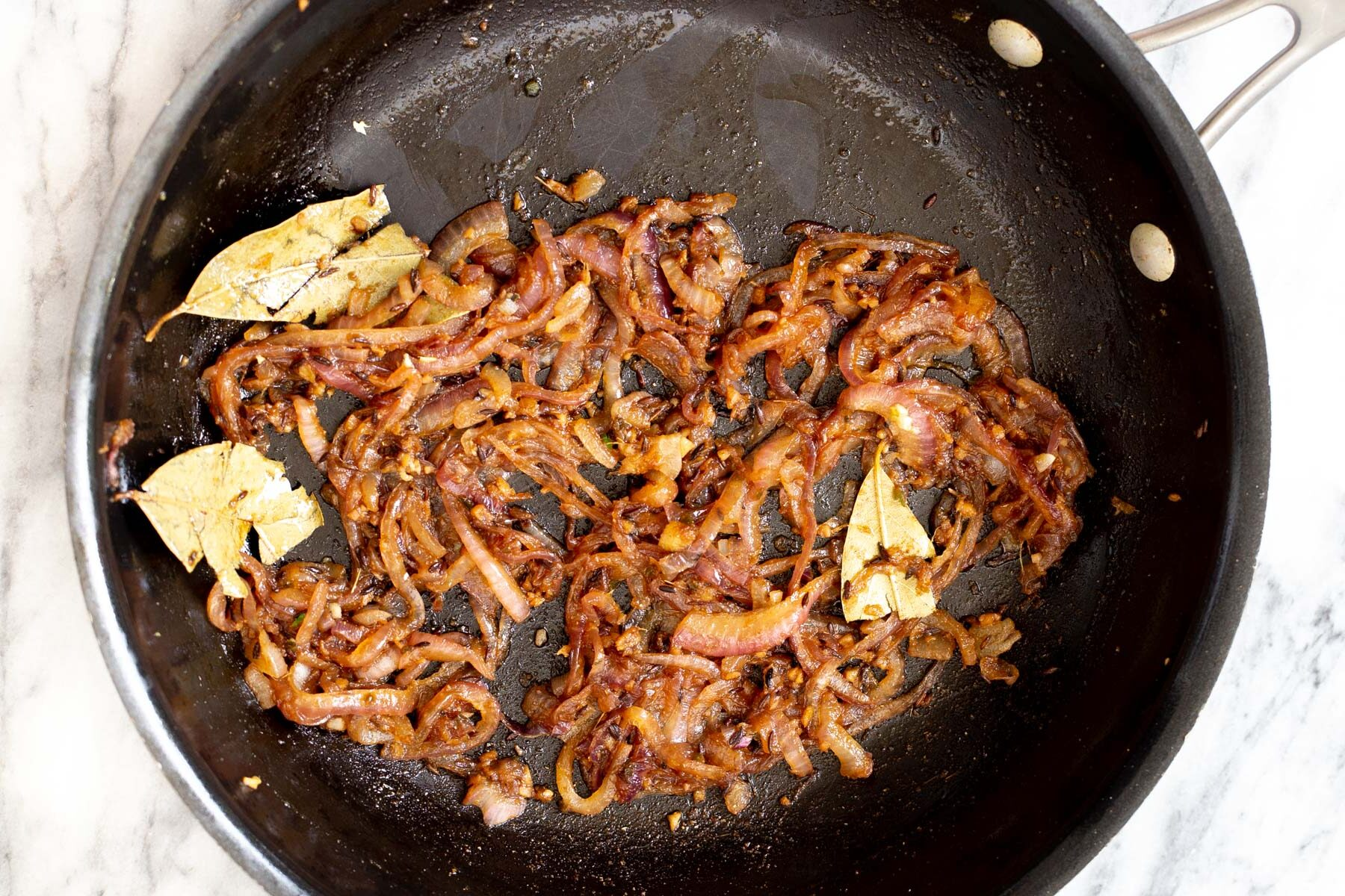 spices and onion being sauteed in a pan