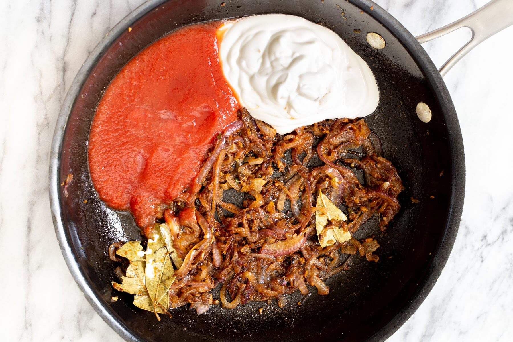 tomato puree and yogurt being added to make Indian gravy in a sauteeing pan