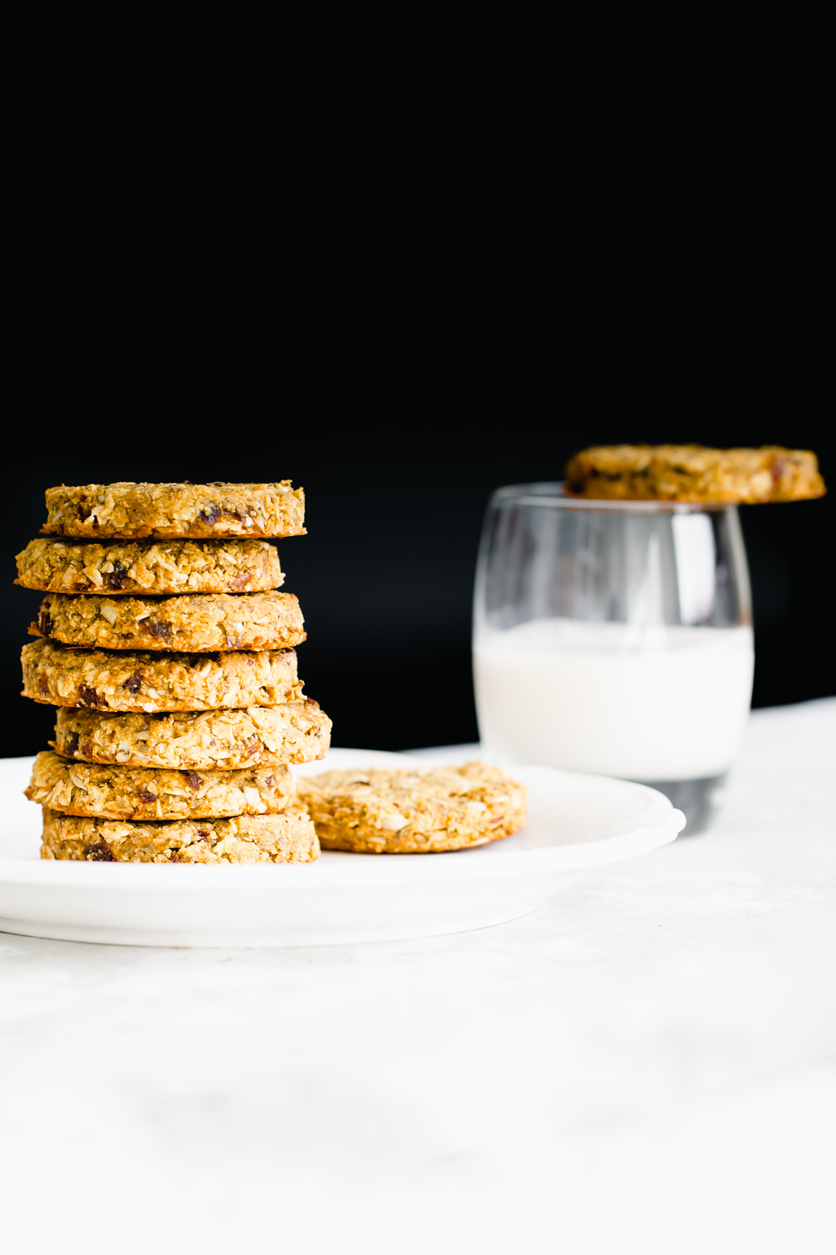 stacked pumpkin breakfast cookies on a white plate with a glass of milk in the background