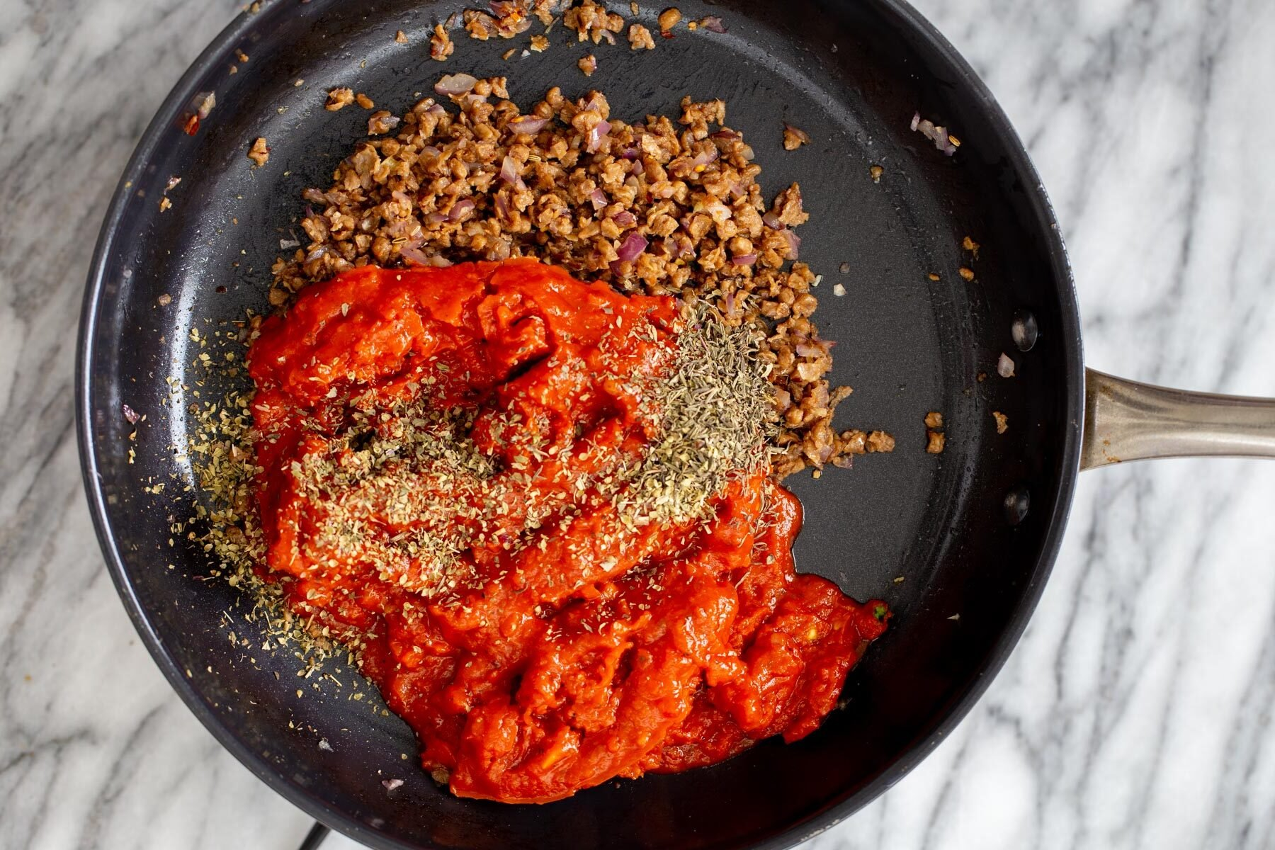 tomato sauce being added to a skillet with vegan meat crumbles