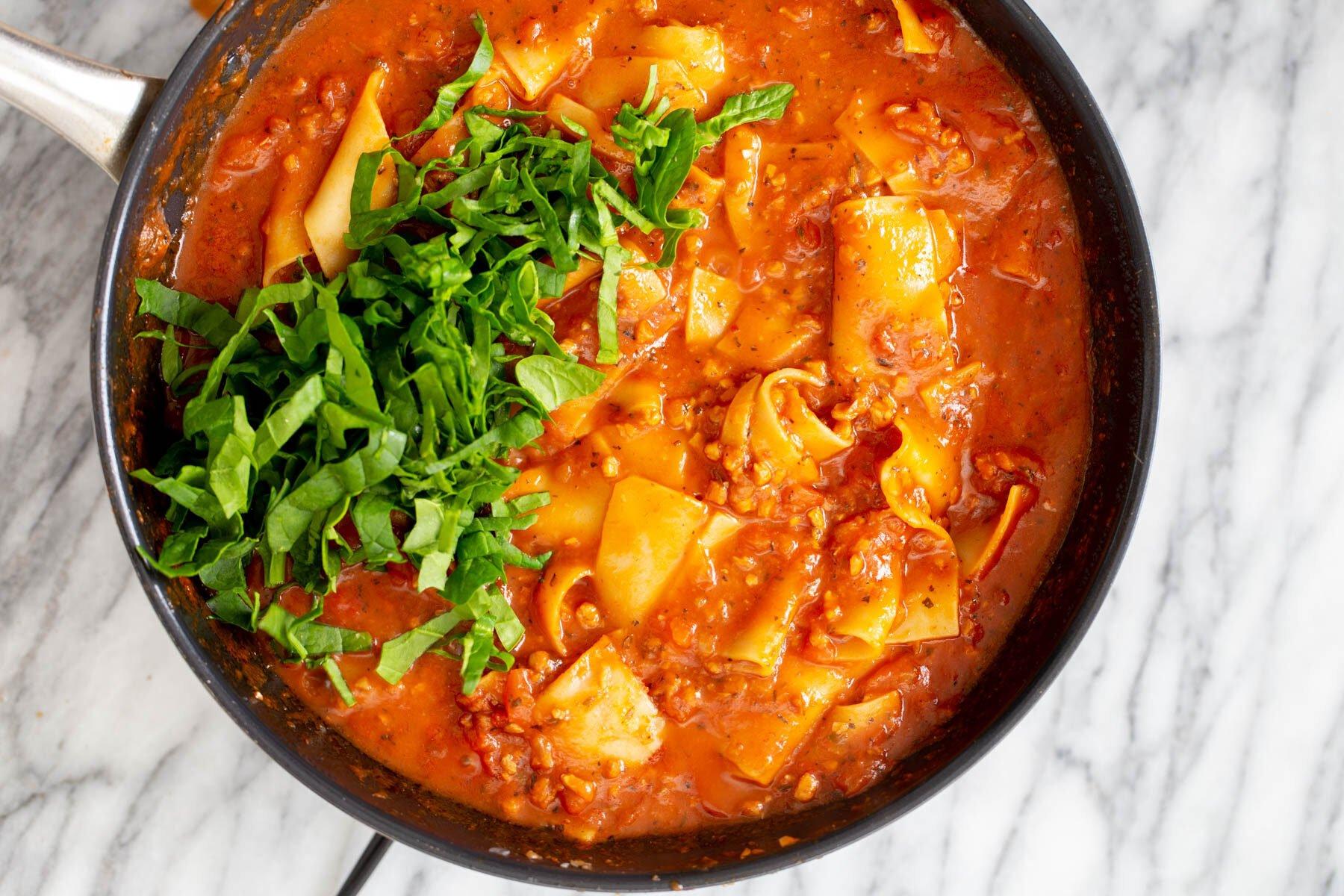 fresh basil being sprinkled over vegan skillet lasagna