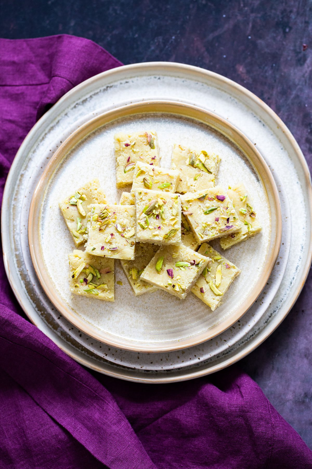 a plate with almond burfi topped with chopped pistachios and almonds