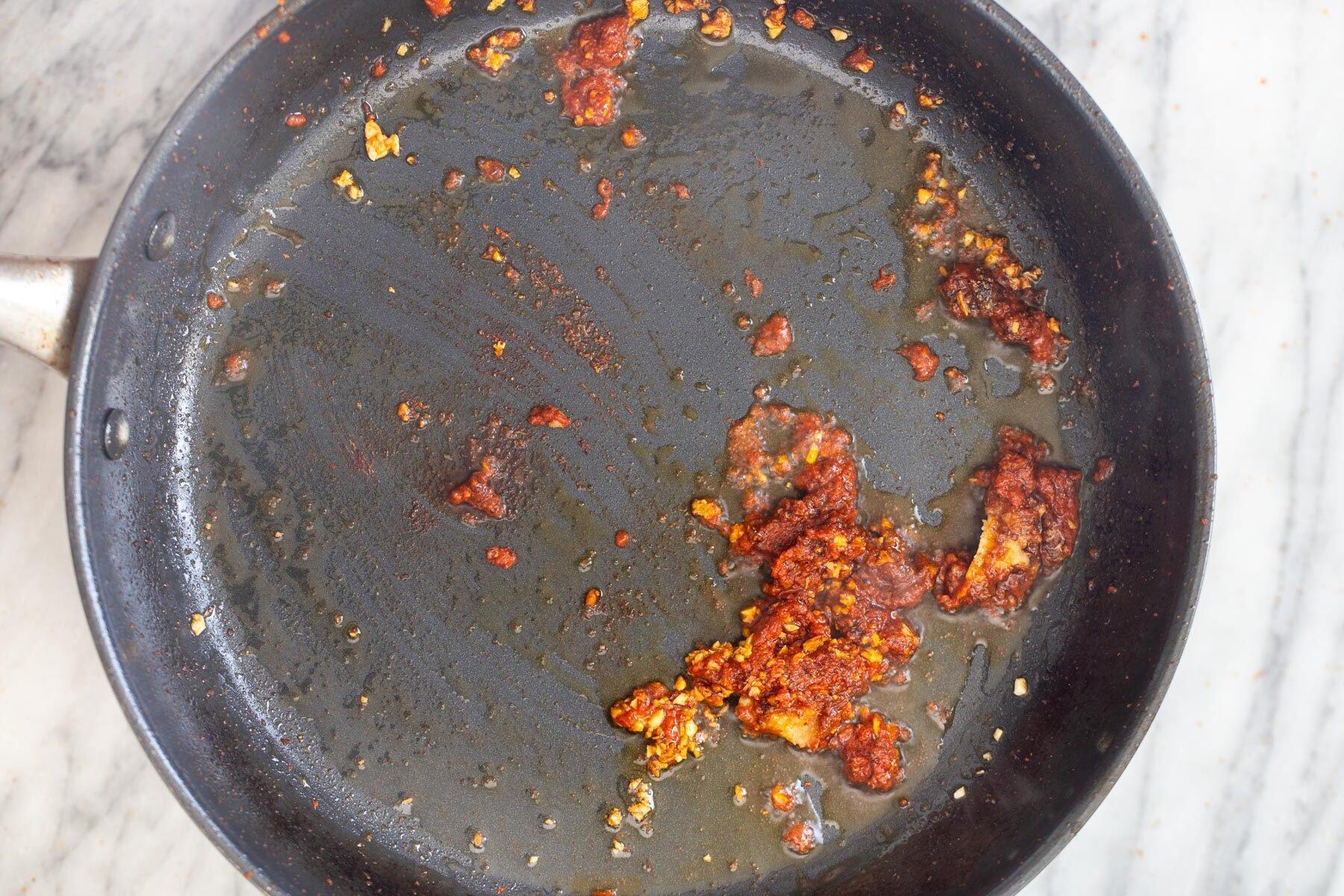 एक सॉस पैन में कीमा बनाया हुआ लहसुन और लाल करी पेस्ट