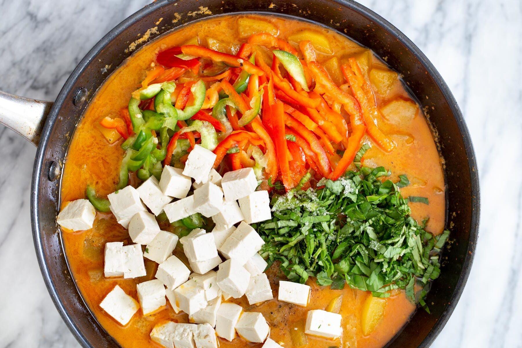 टोफू और सब्जियों को एक सॉस पैन में नारियल शोरबा में जोड़ा जा रहा है