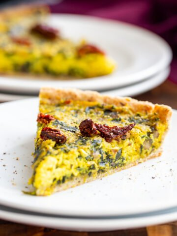 a slice of vegan quiche with spinach and leeks